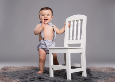 Baby-Standing-againts-Chair-studio-portrait